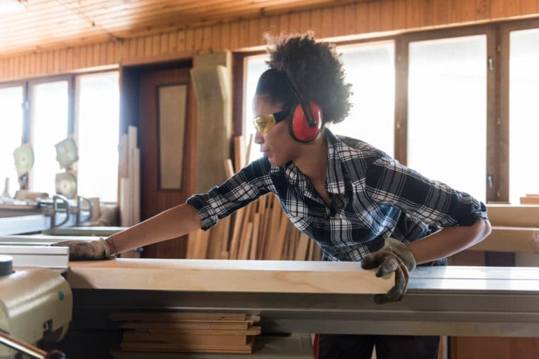 Woman wears hearing protection while working