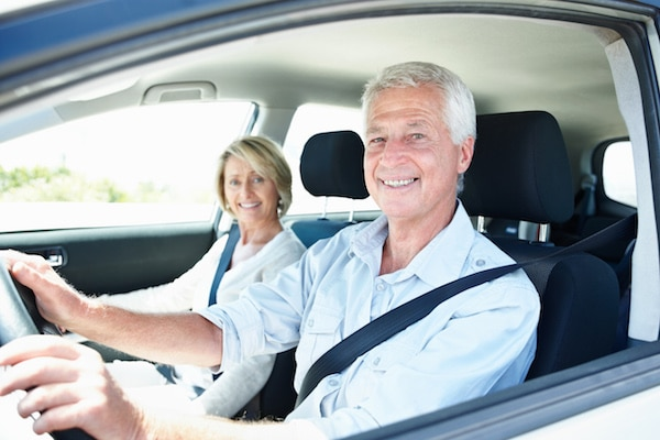 Happy older couple driving a car