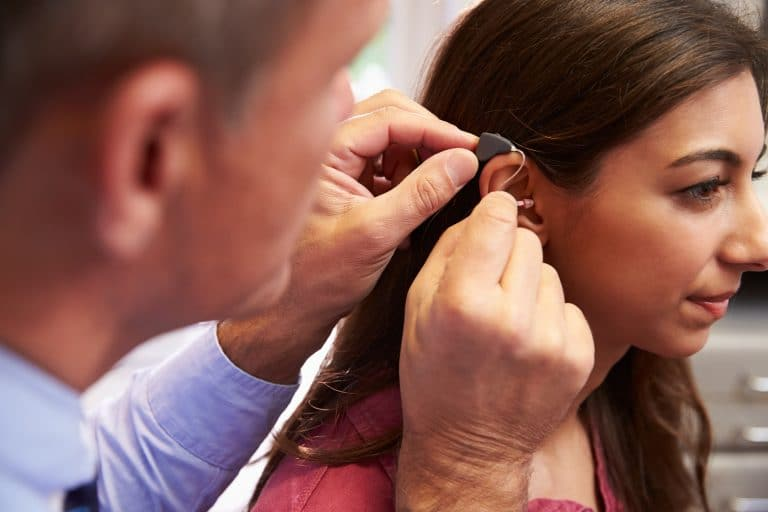 Woman gets a hearing aid fitting.
