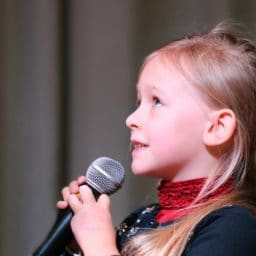 Young girl singing into a microphone