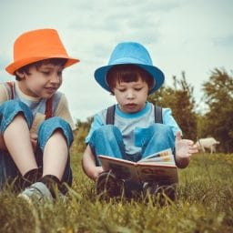 kids reading a book in a field