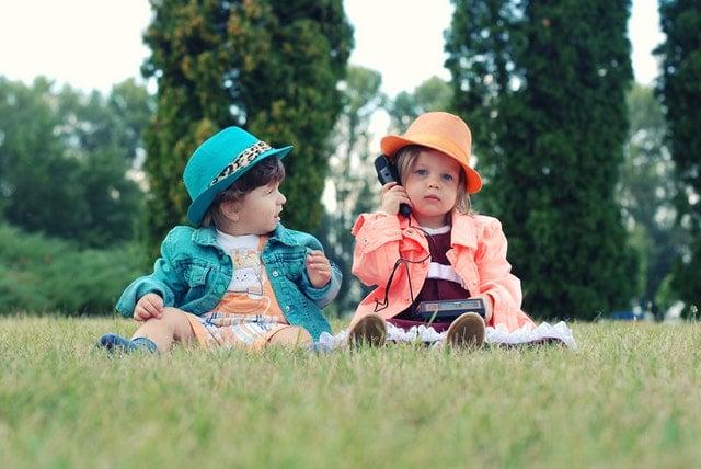 Little kids sitting outside talking on a phone