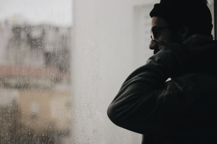 Man looking out a window.